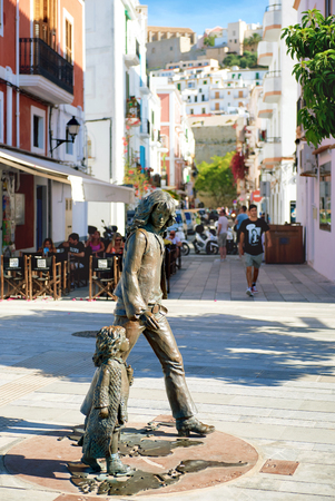 Ibiza, Spain - June 10, 2017: Bronze sculpture honours hippie culture in Ibiza Town. The sculpture is the work of Catalan sculptor Cio Abelli. The bronze sculpture is based on a legendary photograph taken by Toni Riera of a hippie father and his daughter, Editorial