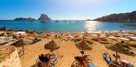 Ibiza Island, Spain - June 12, 2017: People enjoying the summer at Cala d'Hort beach. Cala d'Hort in summer is extremely popular, beach have a fantastic view of the mysterious island of Es Vedra. Ibiza Island, Balearic Islands. Spain Imagens - 86016744