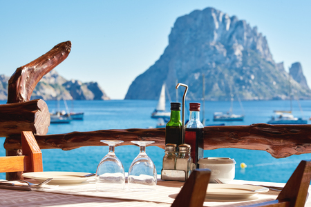 Outdoors restaurant at Cala dHort beach, with a fantastic view of the mysterious island of Es Vedra. Ibiza Island, Balearic Islands. Spain