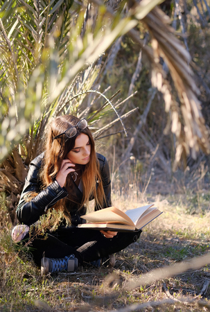Young brunette reading a book outdoors