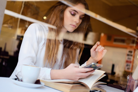 Young brunette with a smartphone sitting in a restaurant