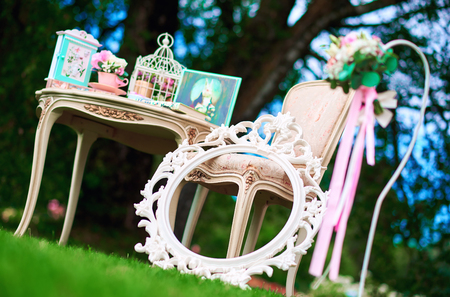Retro styled chair, table and white carved frame. Pretty things, symbols of Alice in Wonderland Stock Photo