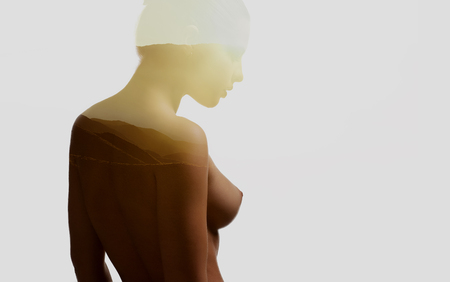Silhouette of a naked woman combined with a mountains during the sunrise. Double exposure, isolated on a white background.