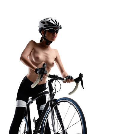 Naked woman with a bicycle on a white background. Studio shot Foto de archivo