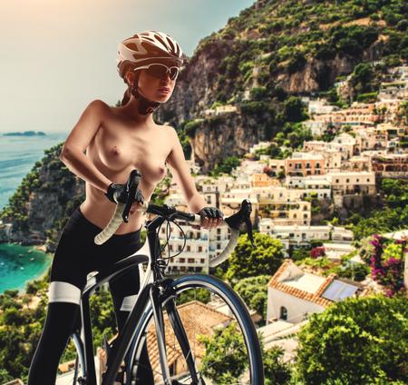 Naakte vrouw met een fiets tegen de kust van Amalfi. Italië Stockfoto - 96777705