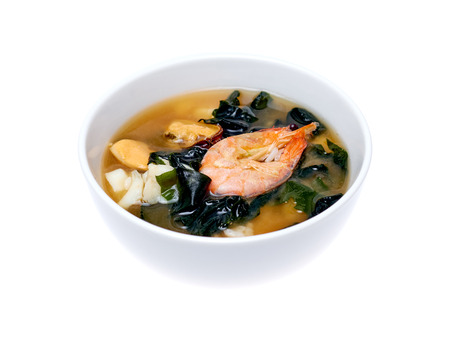 Bowl of seafood soup over white background Stock Photo