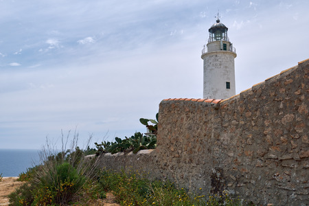 "La Mola lighthouse in the Formentera Island. This lighthouse is famous because, according to the legend, it inspired Julio Verne for its novels ""Héctor Serdavac"" and ""The lighthouse of the end of the world"". Balearic Islands. Spain"