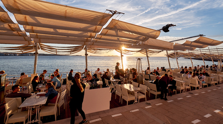 Ibiza Island, Spain - May 1, 2018: Crowds of people meet the sunset at the seafront terrace of Savannah cafe, located on the West Coast of Ibiza. This place is famous for views to the sunsets and lounge music. Ibiza, Balearic Islands. Spain
