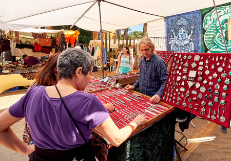 Ibiza Island, Spain - May 2, 2018: Seller and buyers at the Hippy market of Ibiza Island. Stall selling fashion accessories and silver jewellery with precious gems. Hippy market organised since the 1970s by the hippy community. Balearic Islands Spain