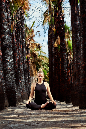 Young woman in black sportswear sitting in lotus position and meditating outdoors. Woman in early gestation. Pre natal exercising, healthy lifestyle. Attractive blond woman in tropical nature, path lined with black trunks of palm trees, unusual scenery. Imagens