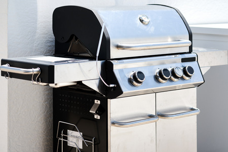 Stainless steel gas grill bbq barbecue. Cooking meat, fish, vegetables in summertime gatherings