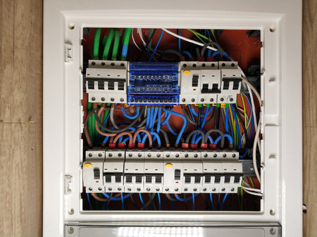 Close up of white frame panel electrical switch board, with colourful cables automatic circuit switchers breakers and fuses