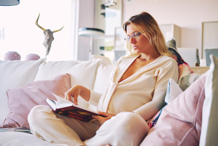 Pregnant young blond woman in casual home clothing sitting in sofa at lounge, sitting room and reading a book about maternity or chicklit, womans novel at home. Relaxation, leisure, hobby lifestyle, free time habits concept