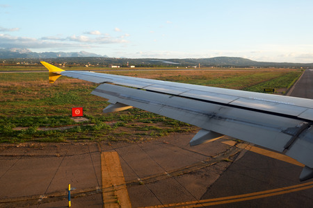 Airplane riding on takeoff strip in the airport, view from airplane window. Spain