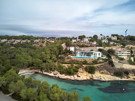 Rich villas on the Cala del Mago coastline with green transparent clear sea water, cloudy weather. Mallorca or Majorca, Balearic Islands, Spain