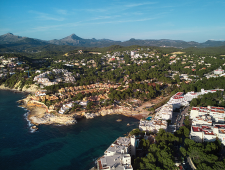 Aerial panoramic view Costa de la Calma shoreline, turquoise clear green water of Mediterranean Sea. Hillside villas between pine forests, mountain range in valley. Mallorca, Majorca, Balearic Spain