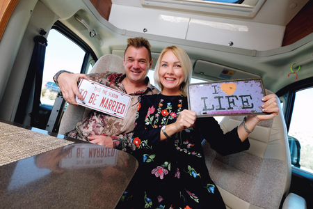 Cheerful laughing middle age family positive travelers couple sitting inside of camper holds hippy retro styled number plate or license number with text This the season to be married and I love life
