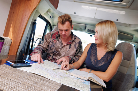 Middle aged married couple talking about future adventure planning route looking at map sitting inside of recreational vehicle motor home trailer. Active lifestyle, traveling by motor vehicle concept