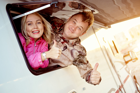Married middle-aged couple family show thumbs up finger up getting out from caravan recreational vehicle motor home trailer window looking at camera feels happy and satisfied. Tourism and trip concept