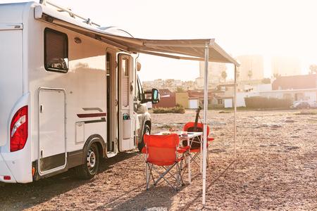 レクリエーション車両キャンピングカートレーラーの近くのキャノピーの下に空の折りたたみ椅子とテーブル。冒険、モーターホームコンセプトで旅行するアクティブな人々 写真素材