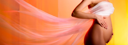 Beautiful pregnant woman touching belly flying fabric over yellow orange color panoramic background. Love and care, childbirth awaiting and new life concept, copyspace for your text Standard-Bild