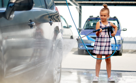 Pretty serious little preschool girl in summer dress helping to parents use coin-operated self-serve car wash, clean auto exterior holding high-pressure sprayer standing outdoors