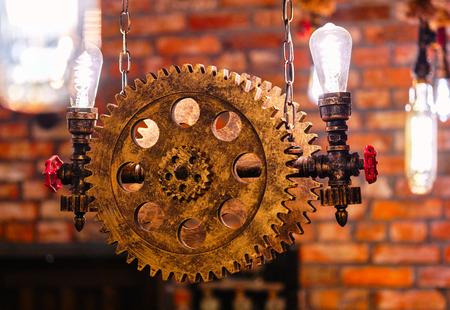 インテリアのスチームパンク建築スタイルのデザイン要素。屋内にぶら下がっている鉄の産業用ギヤの歯車のスプロケット照明照明装置に固定されたランプの球根