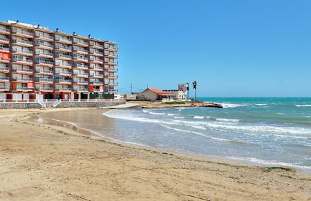High rise building near the Mediterranean Sea, sandy beach coastline of Playa del Cura in Torrevieja city at springtime, no people. Costa Blanca, Province of Alicante, Europe, Spain Foto de archivo