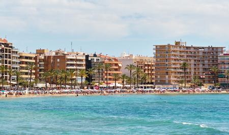 Waterside view blue Mediterranean Sea, vacationers enjoy warm weather sunbath on beach under parasols swim in warm water, crown of people spend time in shoreline Playa del Cura in Torrevieja, Spain