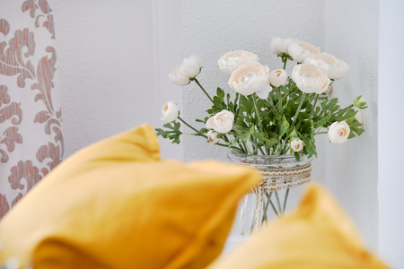Yellow pillows on couch in living room, focus on beautiful flowers on a thin stem in glass vase white ranunculus near wall cute decoration at home, no people
