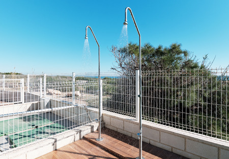 Inside of fenced area two outdoor shower sprinklers is on, water pours on tiled floor outdoors. Photo taken in urbanization near swimming pool or after beach to wash off the sand. Torrevieja, Spain Stock Photo