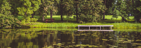 Horizontal image panoramic scenic view summer green landscape with picturesque forest lush lawn wooden pier dock for boats, in pond lake mirrored reflected nature, sunny day, Baltic States