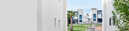 Between two white residential houses view to green lawn of residential urbanization, modern architecture similar townhouses in row, private area, summer landscape horizontal cropped image copy space Imagens - 124867632