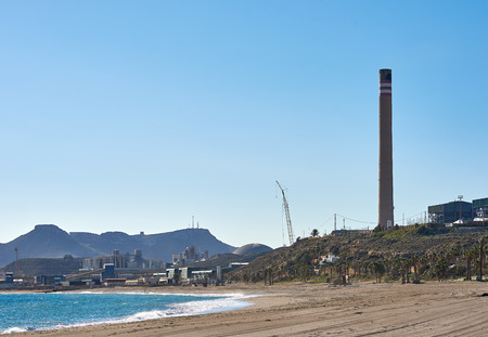 Empty sandy beach, Mediterranean Sea bay blue clear sky and chimney of cement factory in Carboneras. Province of Almeria. Spain Imagens