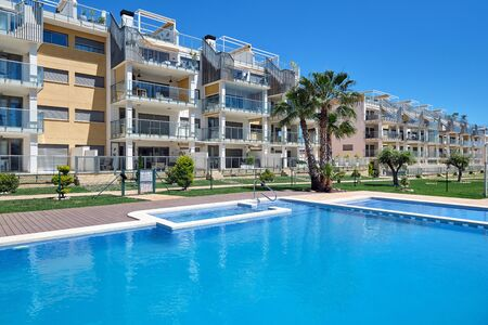 Torrevieja, Spain - April 24, 2019: High rise residential multi-storey house closed urbanization with swimming pool, waterside view, no people. Province of Alicante, Costa Blanca, Torrevieja, Spain