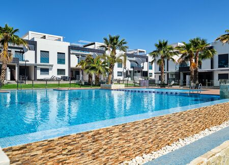Torrevieja, Spain - May 1, 2019: View to new built modern town houses closed urbanization with swimming pool palm trees, luxury residential building exterior, Torrevieja, Province of Alicante, Spain
