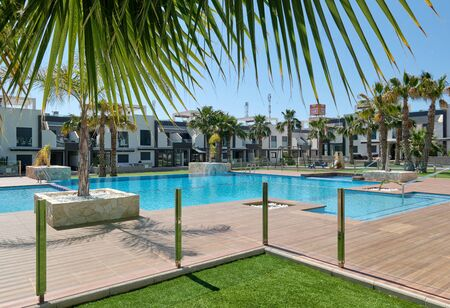 Torrevieja, Spain - May 1, 2019: View to new-built modern town houses closed urbanization with swimming pool palm trees, luxury residential building exterior, Torrevieja, Province of Alicante, Spain