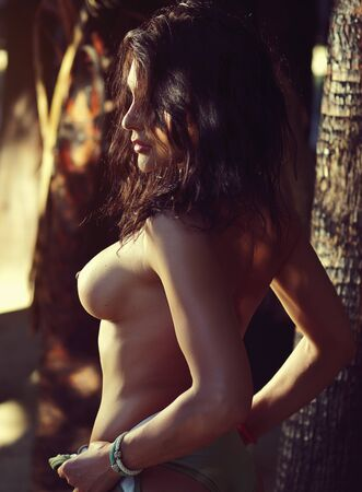 Side view naked 30s woman bare breast posing on tropical trees palm tree trunks background, sunlight illuminates her body
