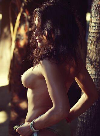 Vista lateral 30s mujer posando sobre fondo de troncos de palmeras de árboles tropicales, la luz del sol ilumina su cuerpo Foto de archivo