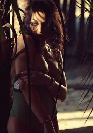 Naked 30s female sexy brunette wearing swimsuit bare breast posing in tropical forest alone