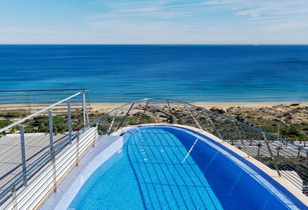 Waterside view part of swimming pool and view to the sandy beach Mediterranean Sea. Province of Alicante, Costa Blanca, Spain
