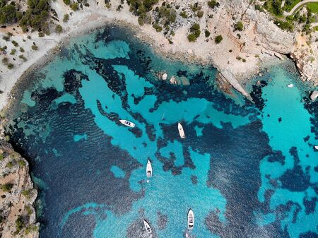Drone point of view directly from above moored yachts on the bright blue bay on the Cala Blanca Andratx in the Palma de Mallorca, rocky coast breathtaking view, Balearic Islands Spain