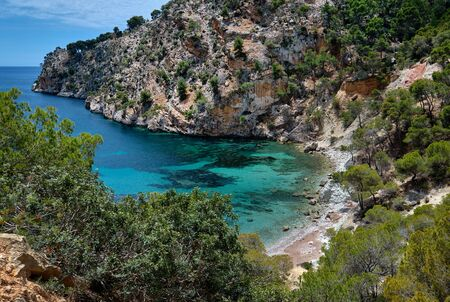 Turquoise bay of Mediterranean Sea located in Cala Blanca Andratx, cove with small stony unspoiled beach and view to mountain surroundings, Mallorca, Baleriac Islands, Spain