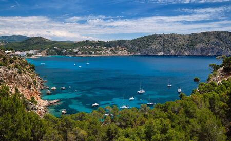 Above view turquoise bay full of moored luxury yachts motorboats in the Mediterranean Sea, picturesque Cala Blanca Andratx, rocky mountains lush greenery Mallorca, Balearic Islands, Spain Banque d'images