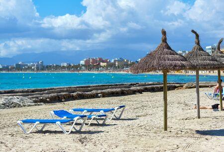 El Arenal city skyline, sandy beach empty sunbeds straw parasols in a row, bright colors blue Mediterranean Sea, Mallorca Island, Baleares, Spain