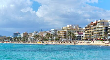 Waterside view El Arenal touristic spanish town, vacationers enjoy warm weather on sandy beach coastline, blue tranquil Mediterranean Sea, sunny day, cloudy fluffy sky. Mallorca Balearic Islands Spain