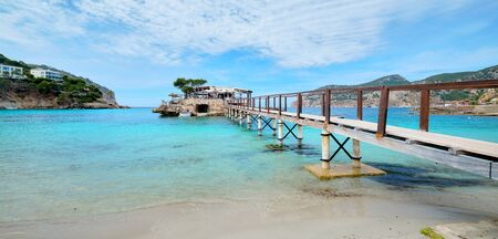 Wooden walkway leading across turquoise Mediterranean Sea in the Camp de Mar small resort village in the municipality of Andratx, Spanish Balearic Island of Mallorca. Spain