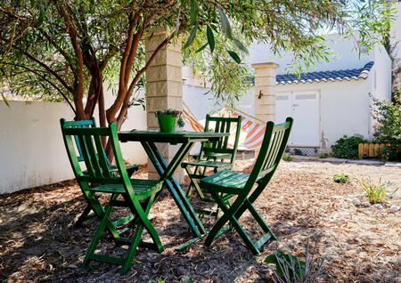 Pretty inner yard with comfortable green color table and chairs under lush green tropical tree and hammock, Spain Imagens