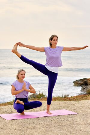 Women do yoga exercises near sea Extended Hand to Big Toe Pose or Utthita Hasta Padangusthasana and Eka Pada Utkatasana standing one-legged asana opens hips improves balance, hobby lifestyle concept