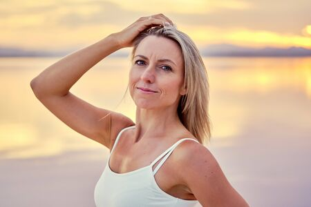 Middle-aged woman pose against cloudy bright sky during sunset looking at camera standing on nature near lake water head shot, healthy sportswoman yoga trainer classes outdoors sporty coach concept